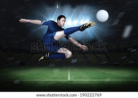 Football player in blue kicking in a football pitch under spotlights