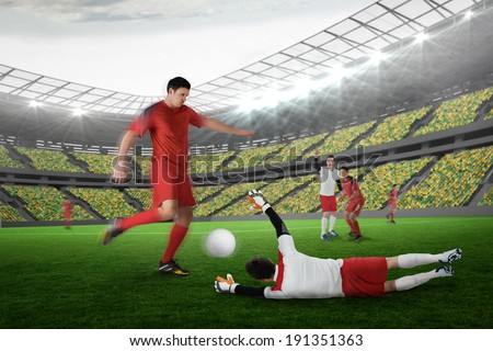 Football player in red kicking against large football stadium with lights