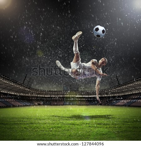 football player in white shirt striking the ball at the stadium under the rain