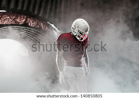 Football player, leaving a smoky tunnel, ready to get on the field