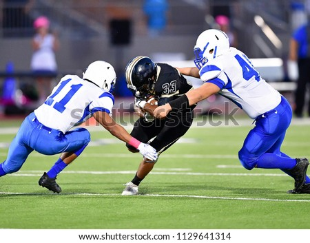 Football player making a tackle during a game #1129641314