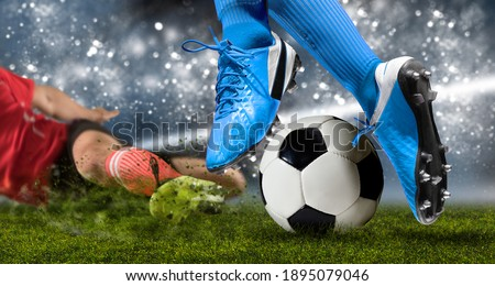 Football player man in action on dark arena background. Soccer player making sliding tackle