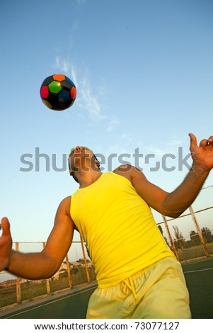 Football player shooting a ball with his head