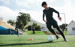 Football player training in soccer field. Young soccer player practicing ball control on training session.