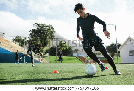 Football player training in soccer field. Young soccer player practicing ball control on training session. #767397106
