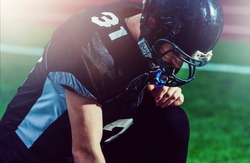 Football player with a black uniform on the scrimmage line on a stadium