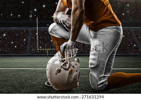 Football Player with a orange uniform on his knees, on a Stadium.