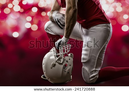 Football Player with a red uniform on his knees, on a red lights background.