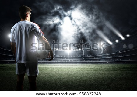 Football player with ball in the stadium