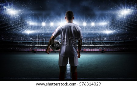 Football player with ball on field of stadium #576314029