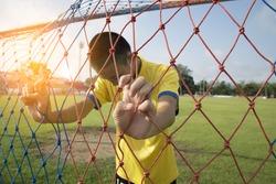 football player young asian boy behind mesh football goal