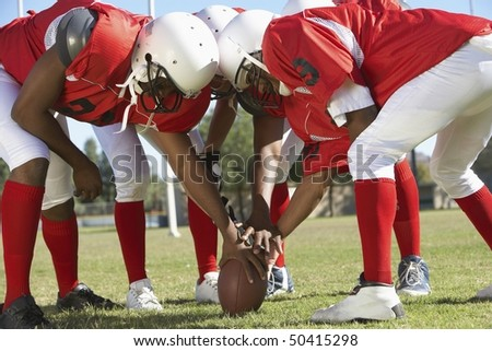Football Players in Huddle around ball