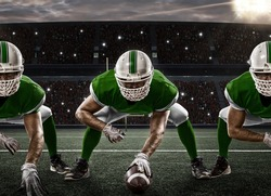 Football Players with a green uniform on the scrimmage line, on a stadium.