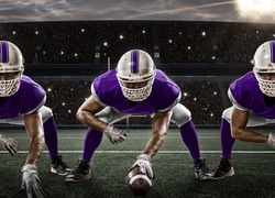 Football Players with a purple uniform on the scrimmage line, on a stadium.