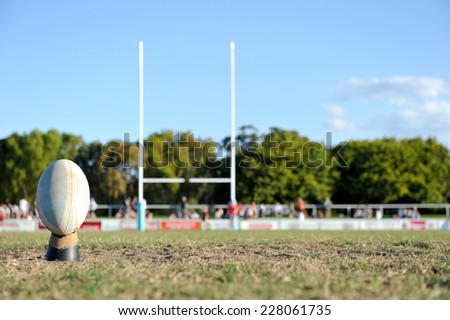 Football ready to be kicked between a set of goal posts on a sporting field.