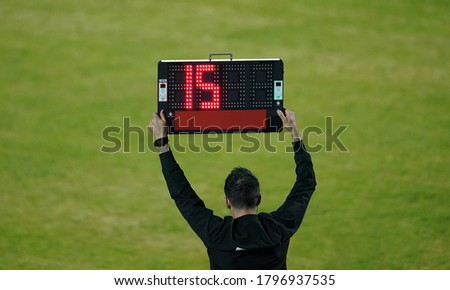 Football referee shows the number display announcing the change of players during the soccer match