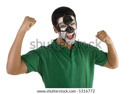 Football's fan with hands up and painted ball on face. He's on white background. Front view. He's looking at camera.