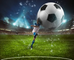 Football scene at night match with player in a white and blue uniform kicking the ball with power