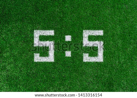 Football score 5:5.White numbers five and five are drawn on the green grass,creative scoreboard #1413316154
