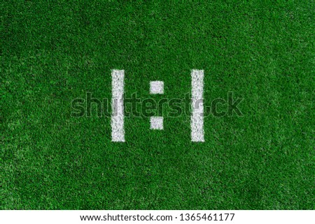 Football score 1:1.White numbers one and one are drawn on the green grass