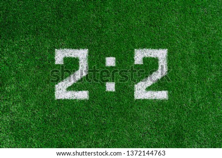 Football score 2:2.White numbers two and two are drawn on the green grass #1372144763