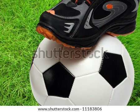 football shoe and soccer ball close-up over green grass field