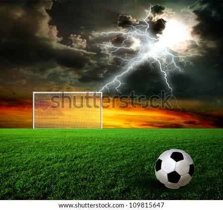 Football, soccer ball on green grass at sunset