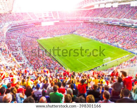 Football- soccer fans cheer their team and celebrate goal in full stadium with open air  with bright lighting beam     -blurred picture.
