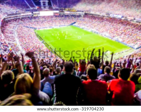Football- soccer fans support their team and celebrate goal in full stadium with open air with nice sky.-blur picture. #319704230