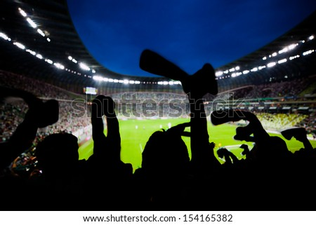 Football, soccer fans support their team and celebrate goal, score, victory. Full stadium