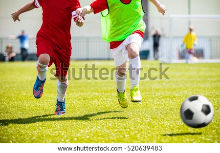 Football soccer match for children. Boys playing football game on a school tournament. Dynamic, action picture of kids competition during playing football. Sport background image