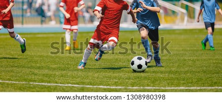 Football Soccer Players Running with Ball. Footballers Kicking Football Match. Young Soccer Players Running After the Ball. Kids in Soccer Red and Blue Uniforms. Soccer Stadium in the Background