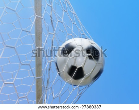 Football spinning in goal against blue sky
