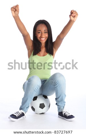 Football sports success for beautiful young African American teenage school girl soccer player, sitting on a ball with arms raised in triumph, with big happy smile.