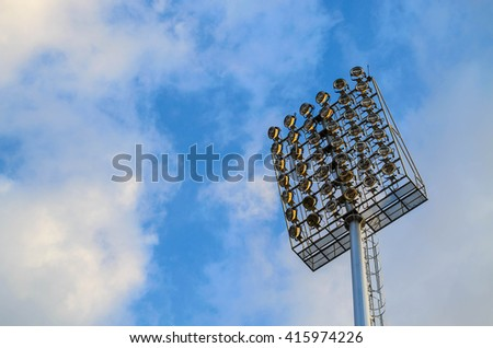 Football stadium spotlight pole on blue sky background
