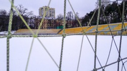 Football stadium with podium and net in winter in the snow