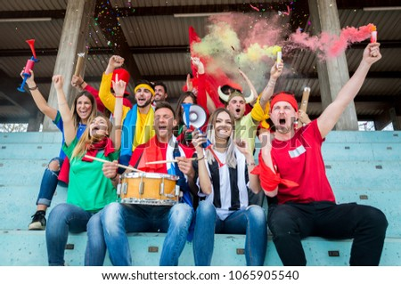 Football supporters at the stadium - Football fans having fun and looking at football match #1065905540