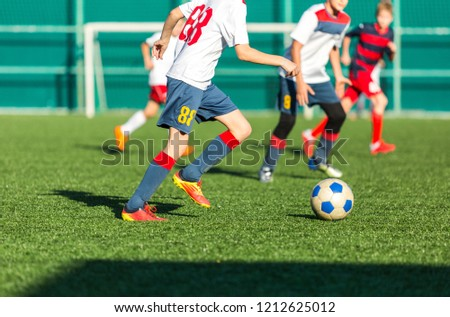 football teams - boys in red, blue, white sportswear play soccer on the green field. boys dribbling. dribbling skills. Team game, training, active lifestyle, hobby, sport for kids concept