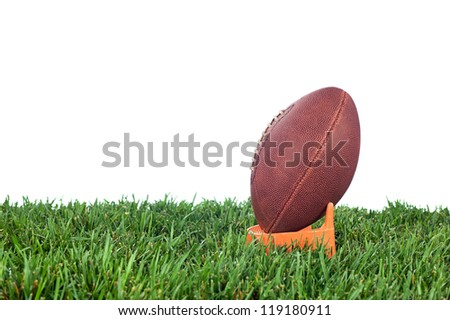 Football tee on green grass waiting for a kick off. White background for placement of copy.