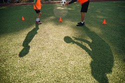 Football training concept. Shadows on the stadium grass of soccer coach trains ball kicks with young football players.
