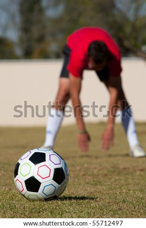 Football with man stretching in background