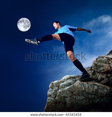 Footballer on the top of mountain at moon night