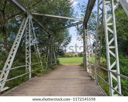Footbridge across Jizera river made of wood and metal steel girder with view on trees and rural summer landscape #1172145598