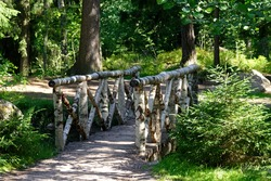 Footbridge over a pond with a railing of birch sticks covered with birch bark in a summer forest.