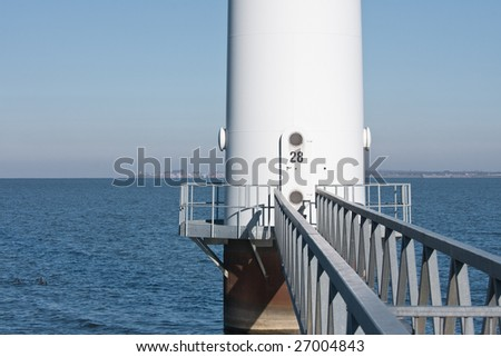 Footbridge to a big windturbine in the Dutch sea