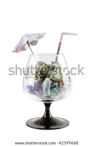 Footed tumbler with different money, umbrella and straw isolated on white as business cocktail for large dealer.