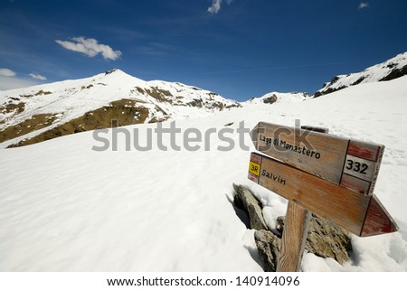 Footpath's wooden signposts in scenic snowy mountain landscape. Location: western Alps, Piedmont, Italy.