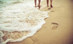 footprint on sand beach of lover walking on the sand beach together, romantic honeymoon trip.
