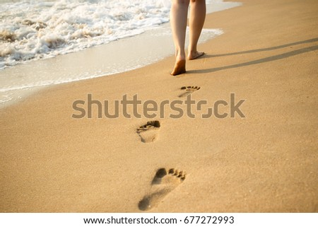Footprint on the beach with sea wave background.