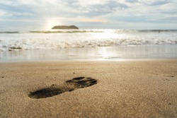 Footprint on the sand of the Pacific beach at sunset